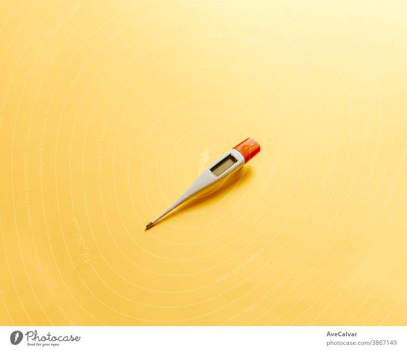 Thermometer über einem flachen und minimal gelben Hintergrund mit Kopierfeld Fieber Gesundheitswesen Krankheit Messung Medizin vereinzelt Temperatur weiß