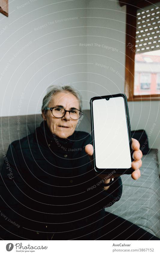 Alte Frau zeigt ein Mobiltelefon mit einem weißen Bildschirm mit Kopierraum Person älter Großmutter copyspace reif Senior Glück in den Ruhestand getreten Anruf