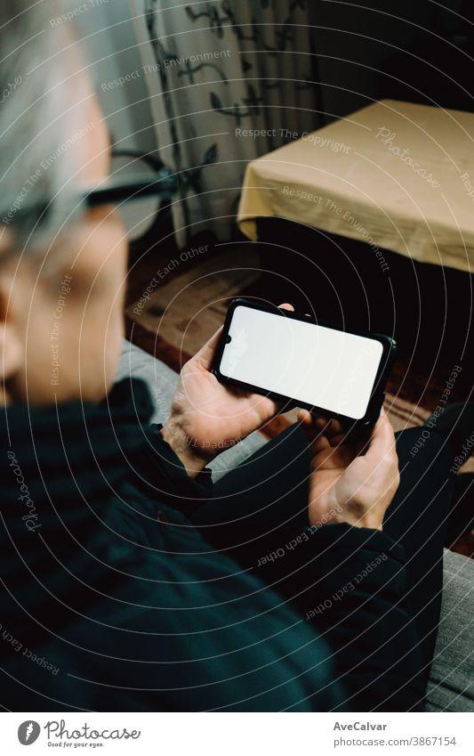 Alte Frau, die ein Telefon mit einem weißen Bildschirm mit Kopierraum in einem Wohnzimmer beobachtet Person älter Großmutter copyspace reif Senior Glück