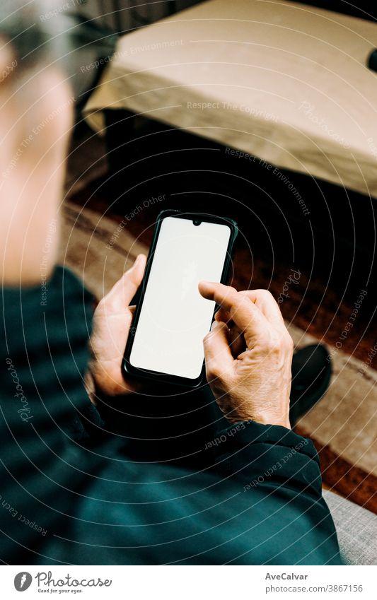 Alte Frau, die ein Telefon mit einem weißen Bildschirm mit Kopierraum in einem Wohnzimmer beobachtet Person Lebensalter älter Großmutter reif Ruhestand Senior