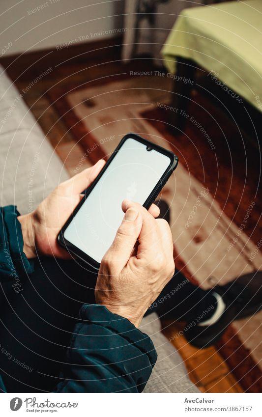 Ein Paar alte Hasen, die in einem Wohnzimmer mit einem Copy-Space-Telefon über einen weißen Bildschirm scrollen Person Lebensalter älter Großmutter reif