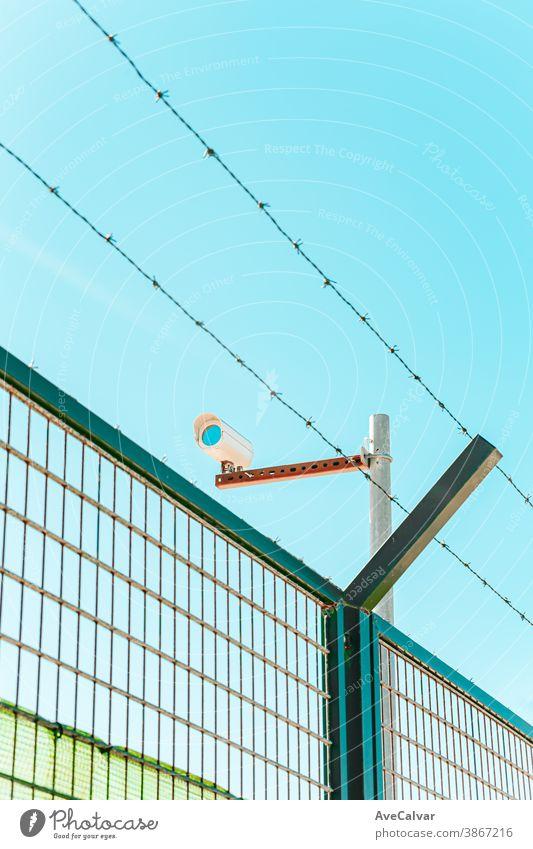 Minimalistische und farbenfrohe Aufnahme einer Überwachungskamera mit einer Mauer und einem Stacheldraht privat Schutz Sicherheit System bewachen Linse Video