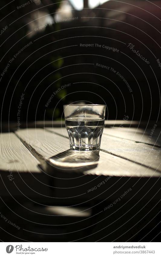 Klares Wasser in einem klaren Glas gegen. Gesundes Essen und umweltfreundliches natürliches Wasser. ein Glas Wasser auf einem Holztisch. trinken Gesundheit