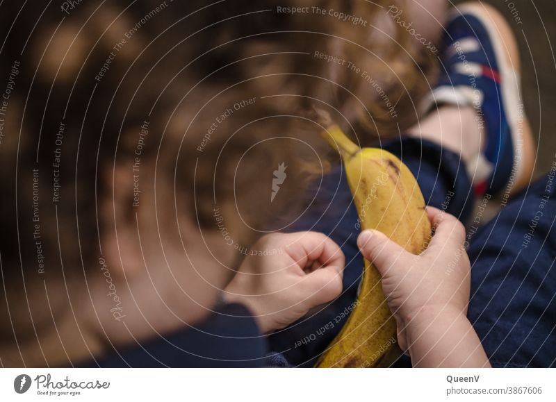 Kind mit einer Banane im Hand Ernährung Kindererziehung KInder Lebensmittel Vegane Ernährung veganer gelb frisch Obst Gesunde Ernährung Vegetarische Ernährung