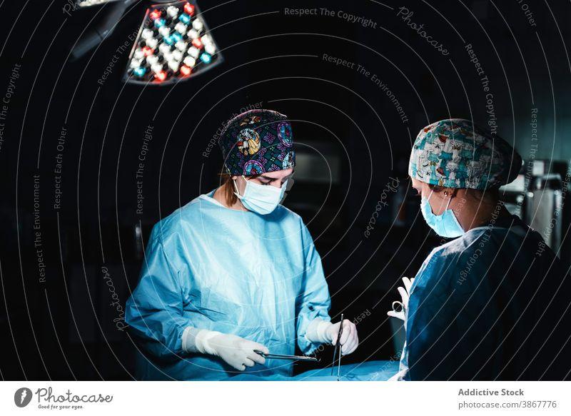 Mediziner bei einer Operation im Krankenhaus Chirurg Operationssaal Sanitäter Team Zusammensein Faser Werkzeug Assistent sticken Krankenpfleger Instrument