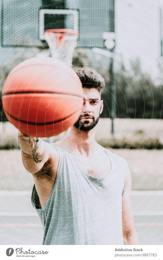 Junger Mann mit Basketball auf Sportplatz Ball selbstbewusst Spieler Streetball Sportpark Vollbart jung ernst Training Spielplatz Athlet Aktivität Lifestyle