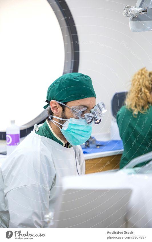Männlicher Zahnarzt in medizinischer Maske und Brille in der Klinik dental mündlich Leckerbissen Mann Arzt Fernglas Stomatologie Zahnmedizin professionell