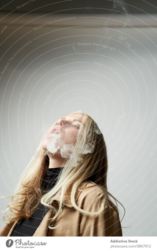 Junge Frau raucht e-Zigarette im Studio e Zigarette Raps Rauch Atelier Verdunstung Stil cool Nikotin Raucherin Habitus selbstbewusst jung schlecht ungesund