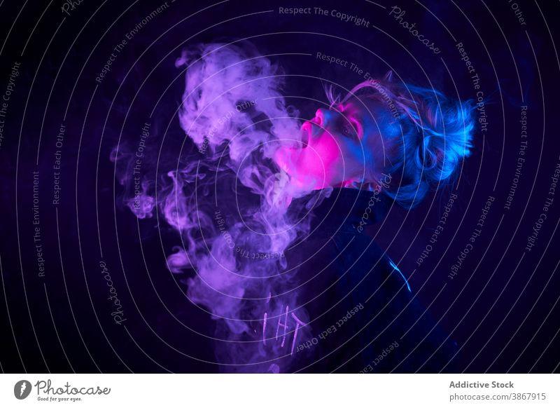Ausdrucksstarke Frau beim Rauchen im dunklen Studio Raps e Zigarette neonfarbig Atelier Licht dunkel Verdunstung cool Stil Nikotin Raucherin Habitus
