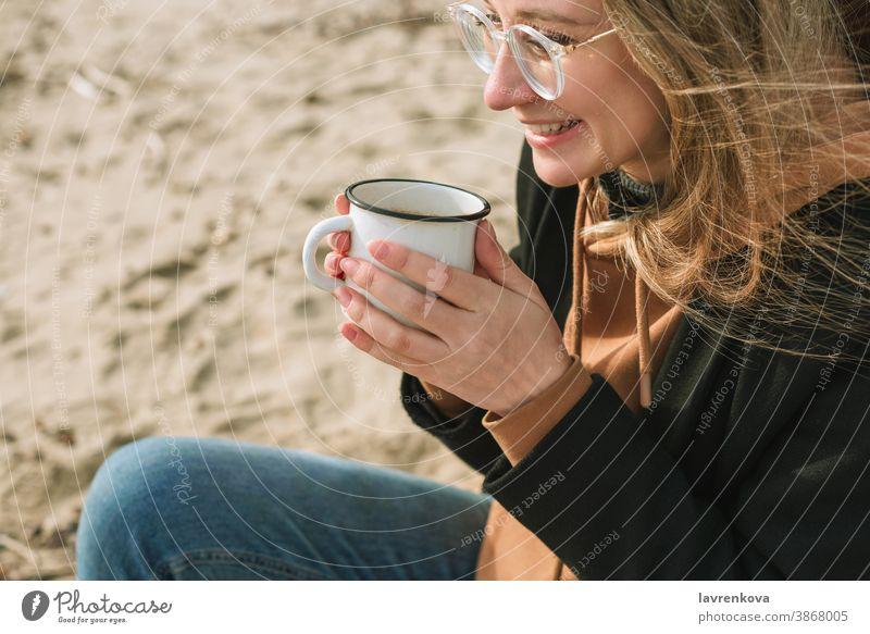 Porträt einer jungen erwachsenen Frau mit Emaillebecher mit heißem Getränk am Strand sitzend Becher Tasse Herbst Winter trinken Glück Tee Lifestyle Lächeln