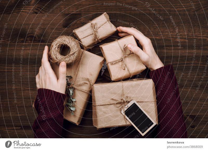 Frauenhände in Pullover mit eingewickelten Geschenken und Schnurrolle auf Holzuntergrund nachhaltig schön Geburtstag Kasten Feier Weihnachten Handwerk