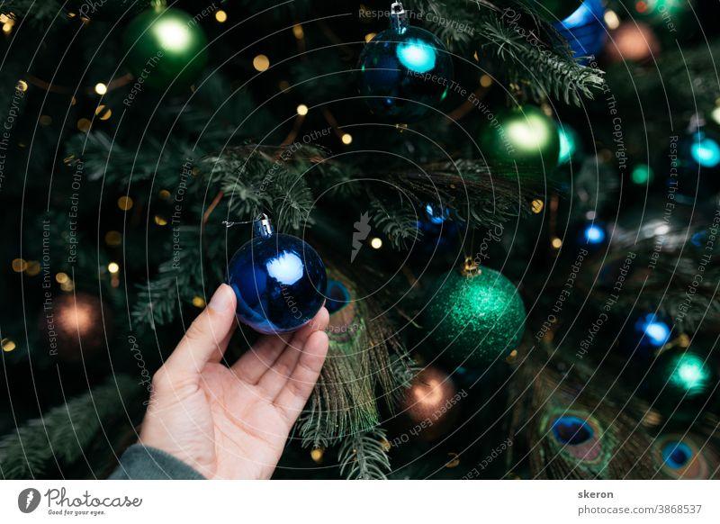 Christbaumschmuck: Weihnachtsschmuck, Lichterketten, die Dekoration in Form einer Pfauenfeder. Konzept: Inneneinrichtung für ein Wohnzimmer mit blauer Wand, Postkarte oder Plakat.