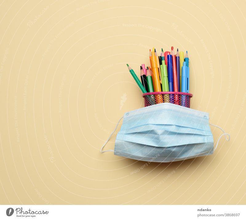 medizinische Einwegmaske und mehrfarbige Stifte und Bleistifte in einem Metalleimer auf beigem Hintergrund Mundschutz Pandemie Schreibstift Prävention schützend