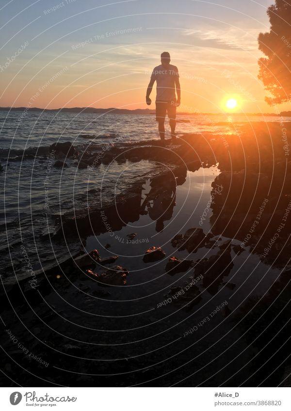 Mann silhouette im Sonnenuntergang  beim Spaziergang auf Steinigen Strand dark body tranquility walk seascape dawn sundown idyllic boy orange twilight beautiful