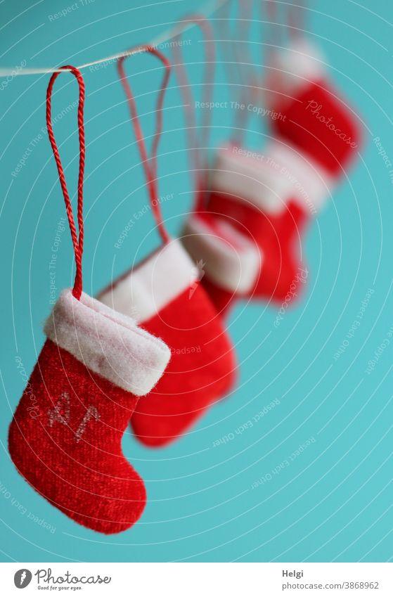 mehrere kleine Nikolausstiefel hängen an einem Seil vor türkisem Hintergrund Weihnachten Advent Weihnachten & Advent Weihnachtsdekoration