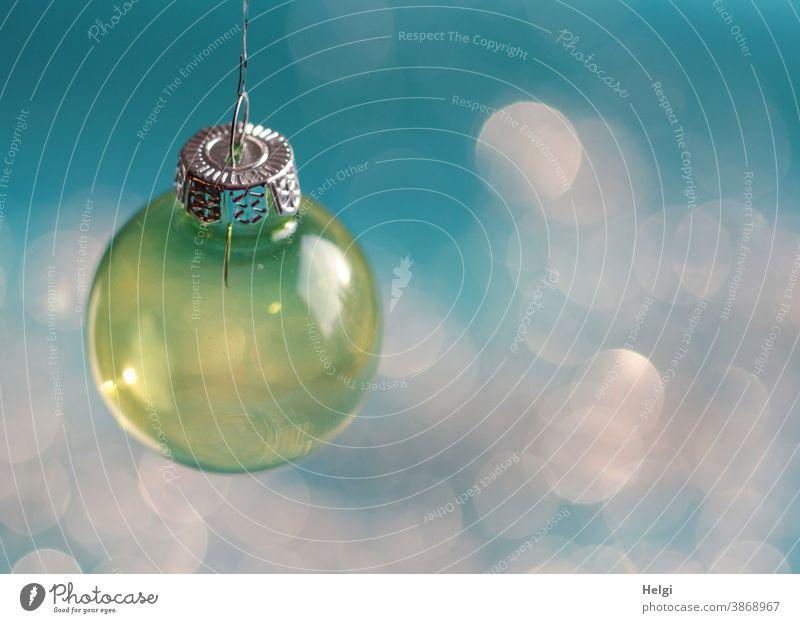 gelbe Christbaumkugel aus Glas hängt vor türkisem Hintergrund mit Bokeh Kugel Glaskugel Weihnachten Weihnachtsbaumkugel Dekoration Weihnachten & Advent