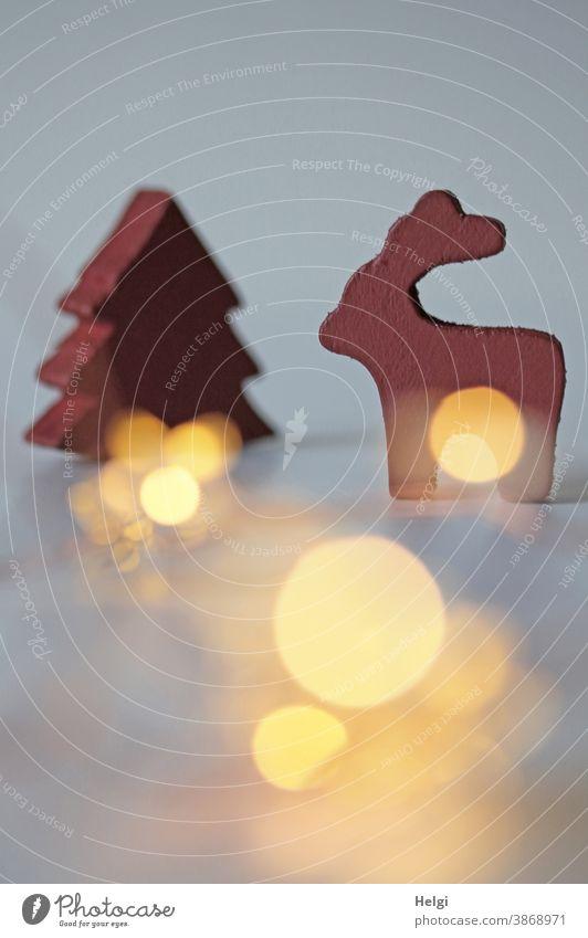 Rentier und Tannenbaum aus rotem Holz vor grauem Hintergrund mit leuchtendem Bokeh Weihnachten Advent Weihnachtsbaum Dekoration Weihnachtsdekoration