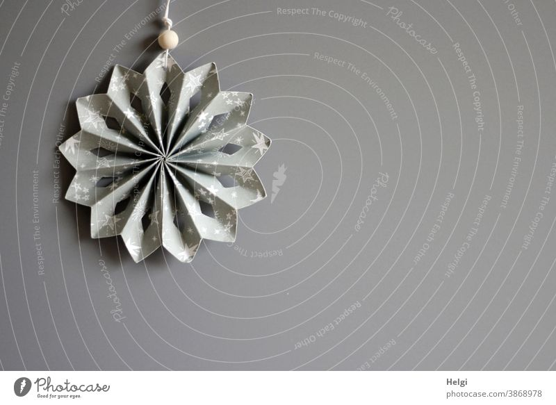 grau-weißer gefalteter Papierstern vor grauem Hintergrund Stern Rosette Dekoration Weihnachten Advent Weihnachtsschmuck Weihnachtsdekoration Textfreiraum rechts