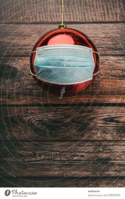 Hintergrund des Weihnachtskonzepts.roter Weihnachtsball mit chirurgischer Schutzmaske Weihnachten Coronavirus covid-19 Weihnachtsbaum Weihnachtshintergrund
