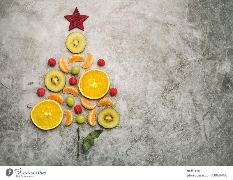 Hintergrund des Weihnachtskonzepts. Obststücke in Form eines Weihnachtsbaums Weihnachten Früchte orange gesunde Ernährung Diät Weihnachtsdessert Kiwi Scheibe