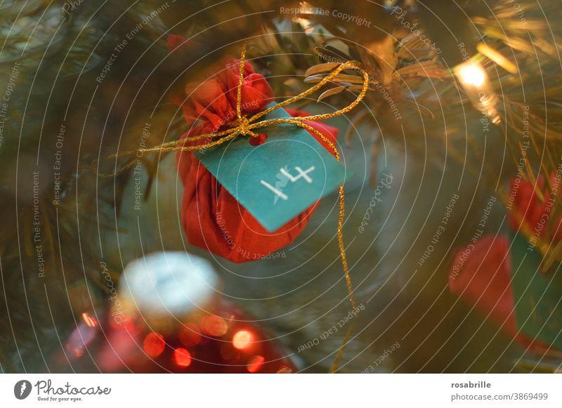 Adventskalender Nr. 14 am Weihnachtsbaum rot vierzehn Nummer numeriert Weihnachten Geschenk Überraschung Säckchen golden Schnur hängen Tanne Tannenbaum