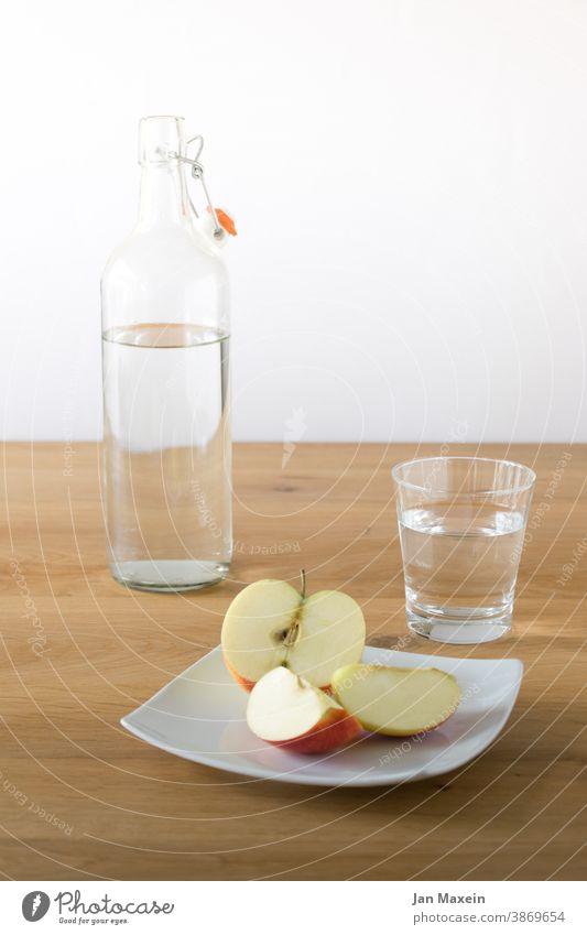 Apfel mit Wasser Flasche Glas Teller Pause Homeoffice nervennahrung Glasflasche Keramik Porzellan Keramikteller frisch klar gesund Bioprodukte weiß rot gelb