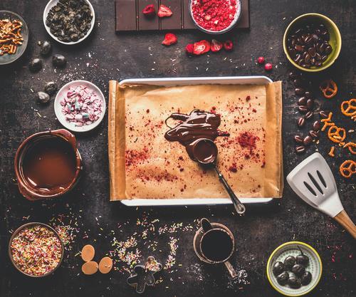 Löffel mit geschmolzener Schokolade auf rustikalem Küchentisch mit verschiedenen Bonbons und Süßigkeiten bar . Ansicht von oben Bar Draufsicht Tradition Raum