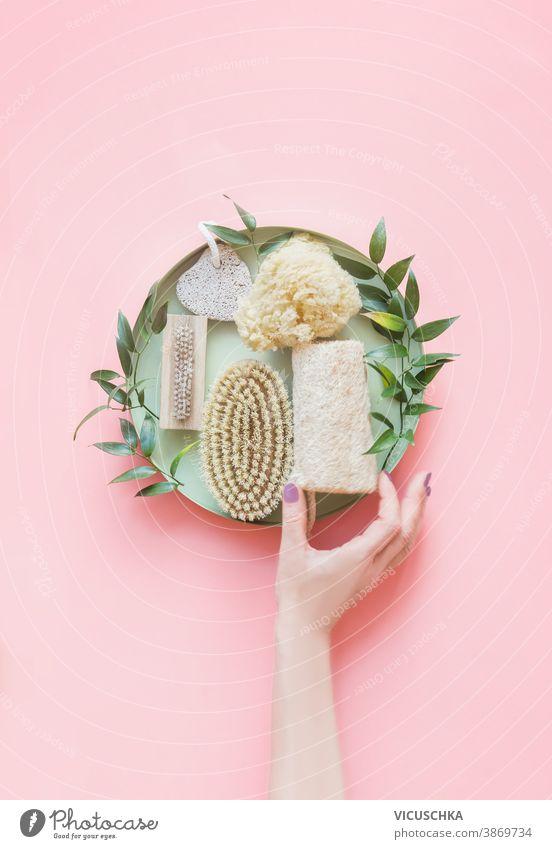 Frauen Hand halten umweltfreundliche Schönheit und Hautpflege Bad Zubehör.  Natürliche Sisalbürste, Holzkamm, Seife, wiederverwendbare Abschminkpads. Null Abfall. Ansicht von oben. Natürliche und Pastellfarben.