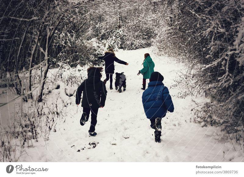 springende Kinder auf einem verschneiten Weg Winterurlaub zugeschneit ein Kind sein Spielen Kindheit Schneelandschaft Vorschulkind Kinderbetreuung Wintersport