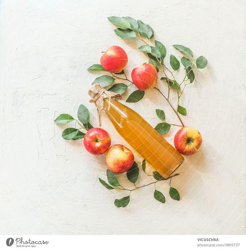 Komposition mit hausgemachtem Apfelsaft in Glasflasche mit Äpfeln und grünen Blättern auf weißem Hintergrund. Ansicht von oben Flasche hausgemachte Speisen Saft