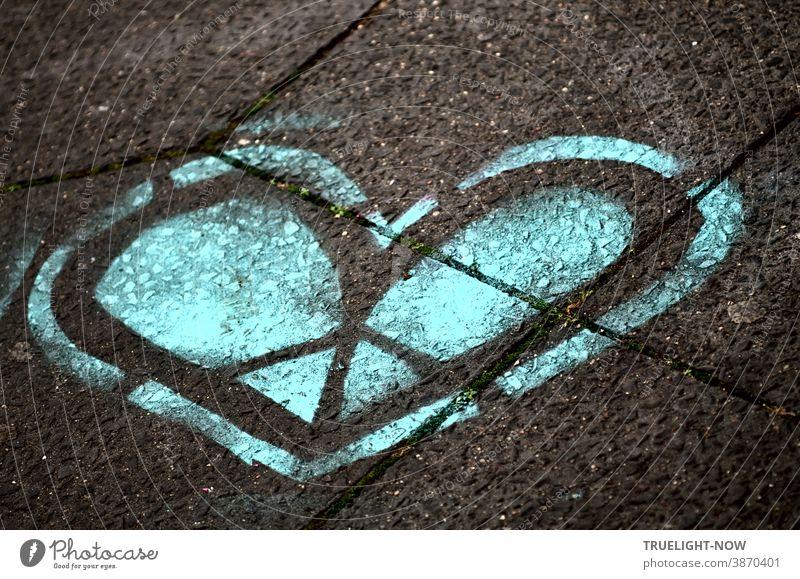 Das blaue Herz. Das kalte Herz. Das Herz aus Stein. Das gespaltene Herz. Das Herz aus Eis. Ein Grafitti Herz in Blau und Schwarz auf graue Betonplatten gesprüht.