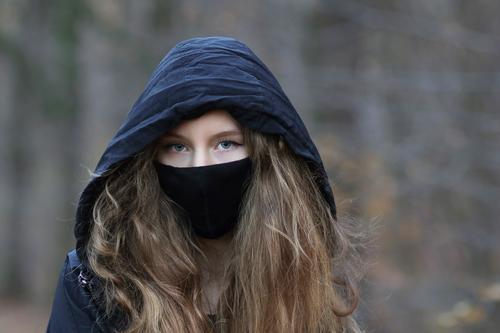Porträt eines Teenager Mädchens mit Kapuze und Mund-Nasen-Bedeckung, Maske I corona thoughts Tag Außenaufnahme Farbfoto Pubertät Gefühle langhaarig 13-18 Jahre