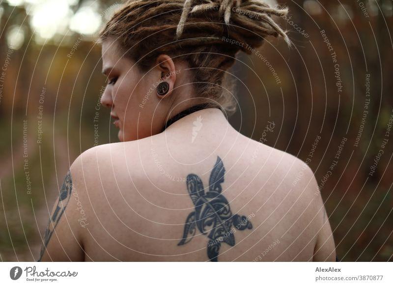 Rückwärtiges Portrait einer jungen Frau mit Dreadlocks und Tätowierungen im Wald dunkelblond Schmuck Piercing Ohrring Oberkörper nackt verdeckt direkt nahe Haut
