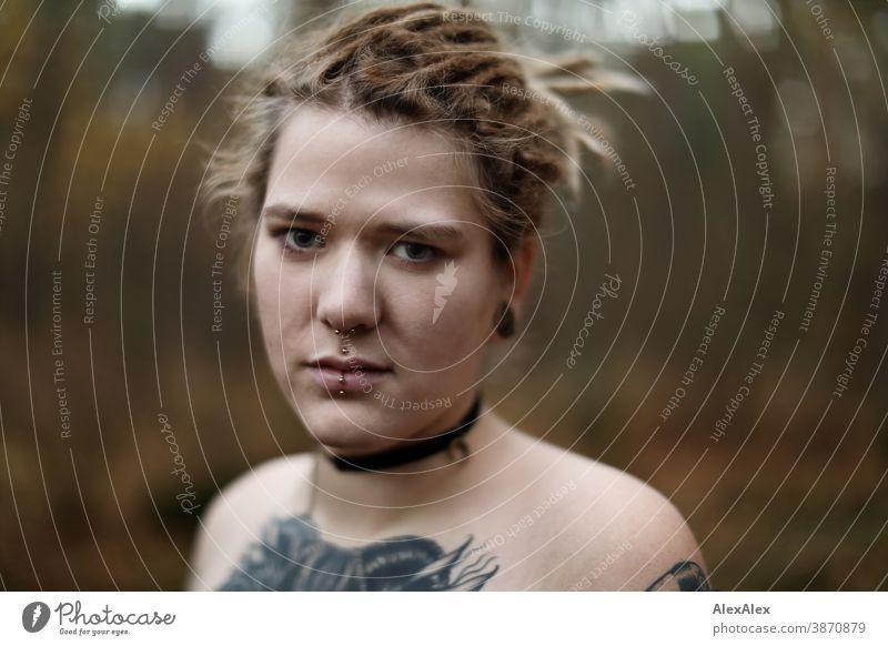 Portrait einer jungen Frau mit Dreadlocks und Tätowierungen im Wald dunkelblond Schmuck Piercing Ohrring Dekolleté Oberkörper nackt verdeckt direkt nahe Haut