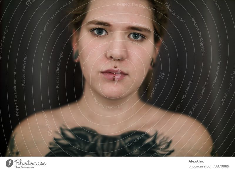 Portrait einer jungen Frau mit Dreadlocks, die eine großflächige Tätowierung eines Ochsenkopfes auf den Dekolletè hat dunkelblond Schmuck Piercing Ohrring