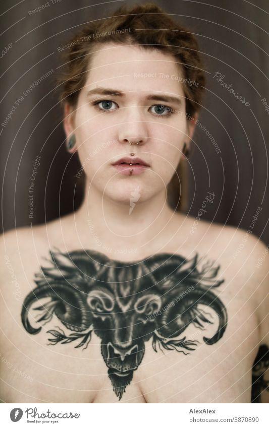Portrait einer jungen Frau, die eine großflächige Tätowierung eines Ochsenkopfes auf den Dekolletè hat dunkelblond Schmuck Piercing Ohrring Dekolleté Brust