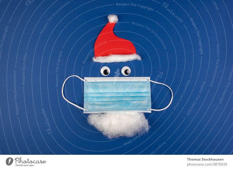 handgemachte Weihnachtsmann-Klausel mit Mottenschutz, Gesichtsmaske, roter Mütze und Bart, als Symbol für die Auswirkungen des Covid-Virus in der Weihnachtszeit