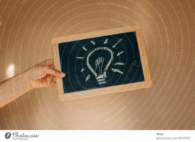 Eine Glühbirne auf eine Tafel gemalt. Konzept eine Idee haben. Kreativität Lösung Inspiration Denken Innovation innovativ kreativ Elektrizität Lampe elektrisch