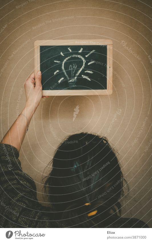 Eine Glühbirne auf eine Tafel gemalt. Konzept eine Frau hat eine Idee. Kreativität Lösung Inspiration eine Idee haben Denken Innovation innovativ kreativ