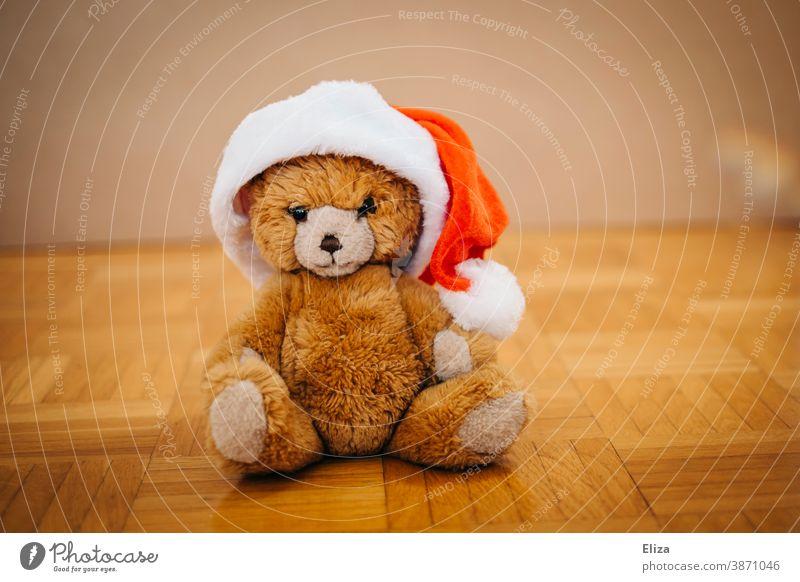 Ein Teddybär mit Nikolausmütze. Konzept Weihnachten mit Kindern. teddybär Kuscheltier Kindheit weihnachtlich Mütze Weihnachtsmannmütze Weihnachtsmütze