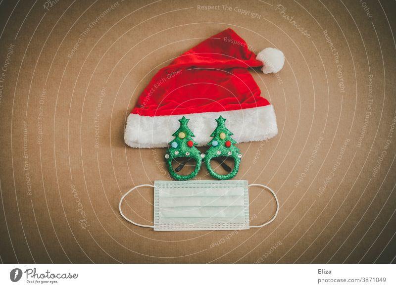 Weihnachten während Corona Konzept mit Weihnachtsmütze, lustiger Brille und Mundschutz Maske. weihnachtlich Weihnachten & Advent Nikolausmütze Mundnasenschutz