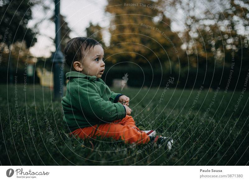 Kleinkind spielt auf dem Rasen authentisch Herbst herbstlich Gras Kind Park Farbfoto Mensch Herbstfärbung Außenaufnahme Herbstlaub Spielen 1-3 Jahre Natur Tag