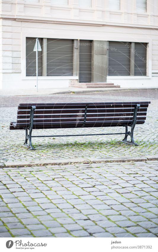 beobachterposition. Bank Textfreiraum unten Tag Sitzgelegenheit Einsamkeit ruhig Pause Gebäude Rollladen Treppe Pflastersteine menschenleer Herbstlaub