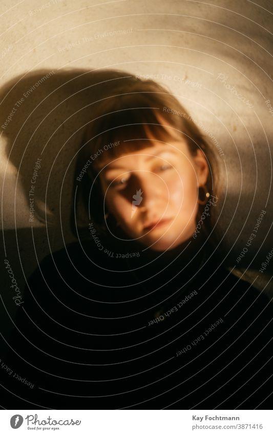verträumte brünette Frau, die mit geschlossenen Augen an der Wand lehnt Erwachsener Appartement attraktiv schön Schönheit braune Haare Windstille lässig