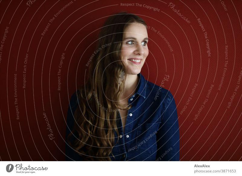 Portrait einer jungen Frau vor einer roten Wand schlank schön brünett lange Haare Schulter Gesicht schlau emotional sehen schauen Blick direkt natürlich
