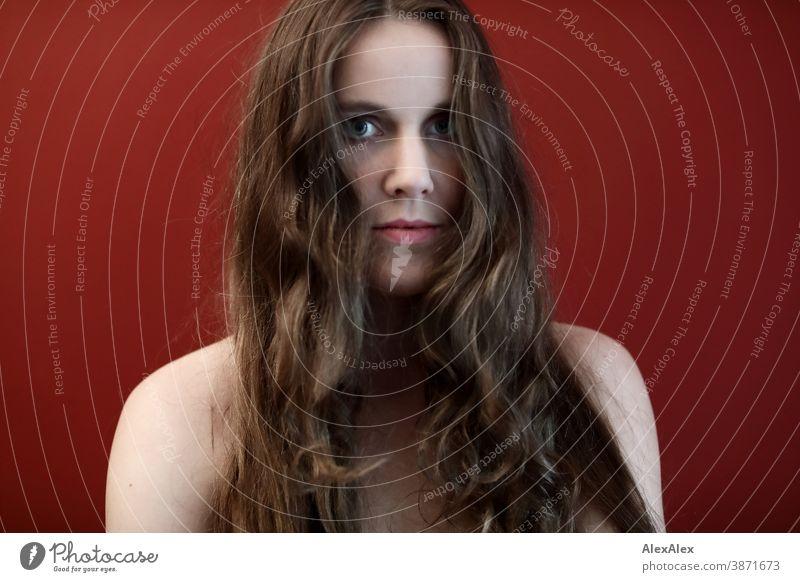 Portrait einer jungen Frau vor einer roten Wand schlank schön brünett lange Haare Schulter Gesicht schlau emotional Haut sehen schauen Blick direkt natürlich