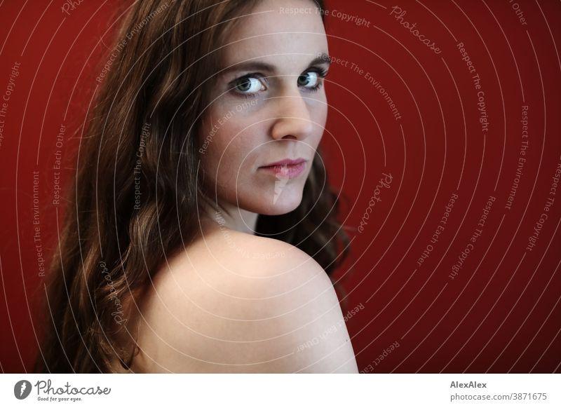 Seitlichen Portrait einer jungen Frau vor einer roten Wand schlank schön brünett lange Haare Schulter Gesicht schlau emotional Haut sehen schauen Blick direkt