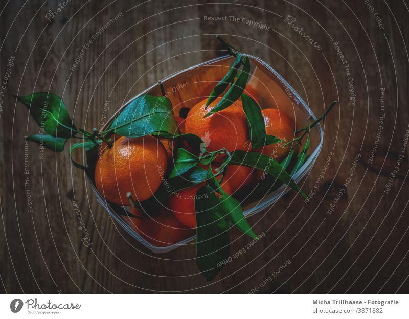 Orangenkorb auf dem Holztisch Apfelsinen Mandarinen Clementinen Früchte Obst Südfrüchte Schale Blätter Stiele Stengel Obstkorb Tisch Tischplatte Weihnachten