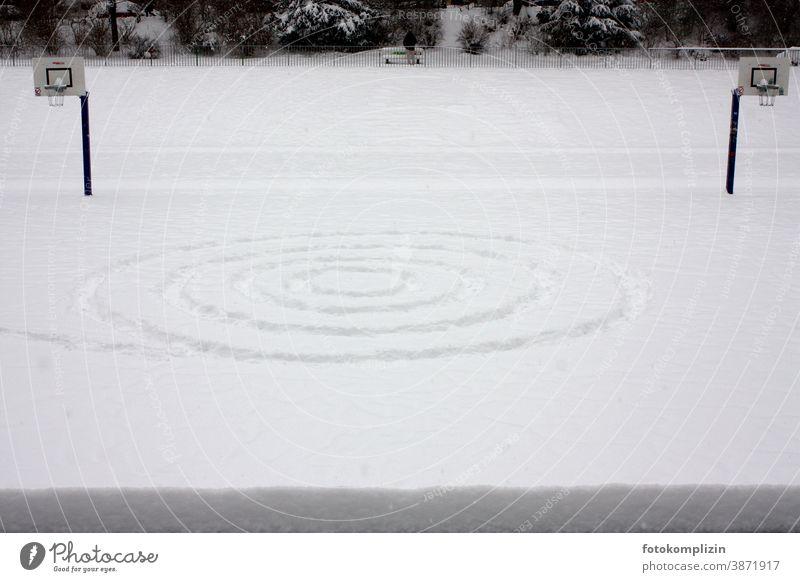 einsame Symmetrie im Schnee schnee Schneespur Wintersport Spuren Basketballplatz basketballfeld Menschenleer Basketballkorb Ballsport Sportstätten