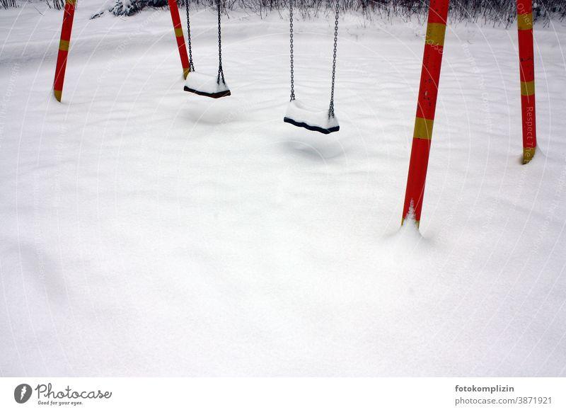 leerer Spielplatz mit zwei Schaukel im Schnee zugeschneit verschneit Winter weiß schnee Wintersport Kinderbetreuung Schneedecke spuren im schnee einsam